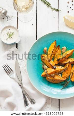 Roasted sweet potatoes on blue plate from above. Wine, dip, lemon and rosemary around. White wooden planked table as background. - stock photo