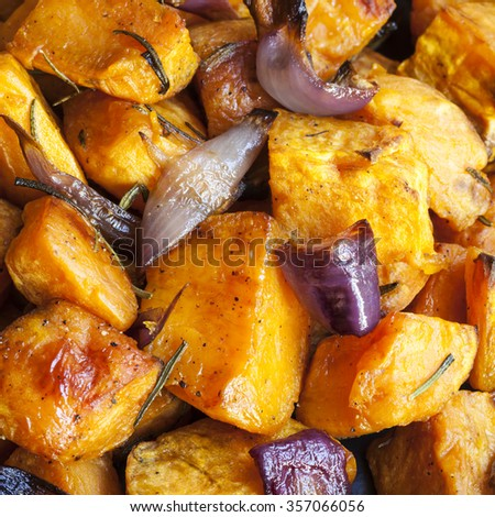 Roasted sweet potatoes with red onions and rosemary. - stock photo