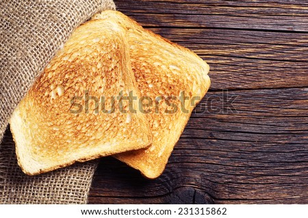 Roasted toast bread on wooden background closeup. Top view