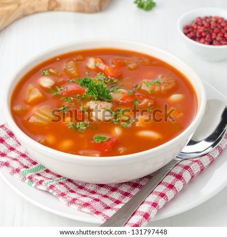 roasted tomato soup with beans, celery and sweet pepper garnished with fresh parsley closeup