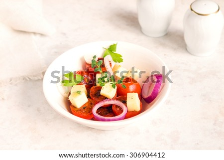 roasted tomatoes, cheese, onion and herbs salad in white bowl