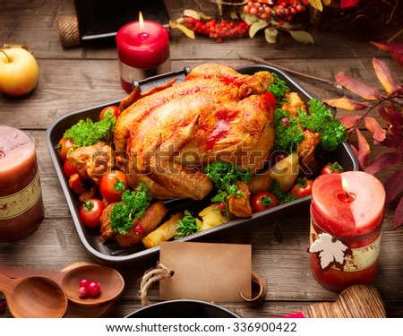 Roasted turkey garnished with Potato, Vegetables and cranberries on a rustic style table decorated with autumn leaves and candles. Thanksgiving Dinner - stock photo