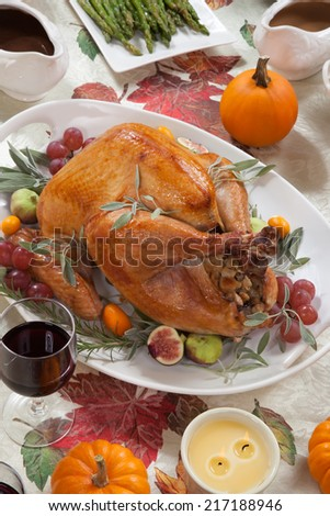 Roasted turkey on a server tray garnished with fresh figs, grape, kumquat, and herbs on fall harvest table. Red wine, side dishes, pie, and gravy. Decoraded with mini pumpkins, candels, and flowers.  - stock photo