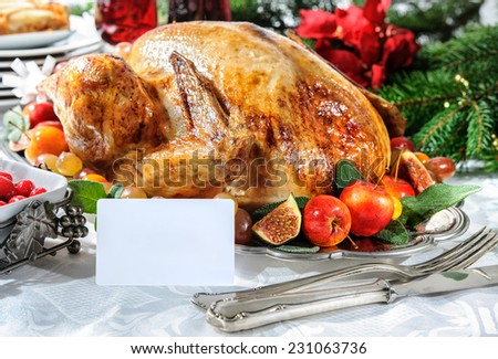 Roasted turkey on holiday table, empty tag and Christmas tree with ornaments - stock photo