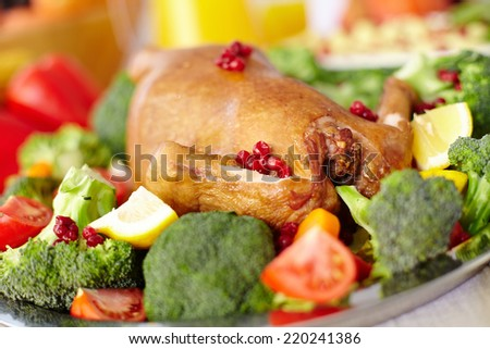 Roasted turkey with cranberries, tomatoes, lemon and broccoli on tray - stock photo