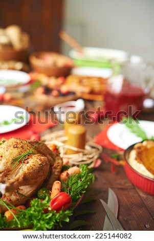 Roasted turkey with pepper, carrots and greenery on festive table - stock photo