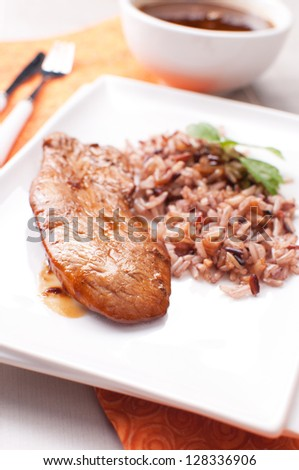 Roasted turkey with sauce and brown and red rice - stock photo