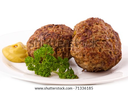 Roasted two meatballs with blob of mustard. Isolated on white