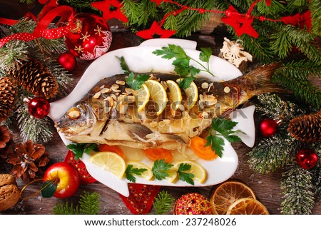 roasted whole carp stuffed with vegetables and almonds on wooden table for christmas-top view  - stock photo