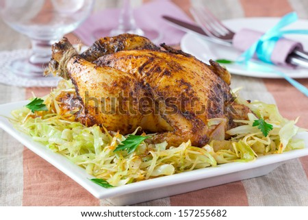 Roasted whole chicken with golden crust and garnish of stewed cabbage, tasty homemade dinner - stock photo