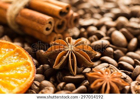Roasted whole coffee beans background with cinnamon, star anise and dried orange - stock photo