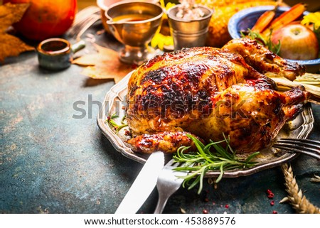Roasted whole turkey or chicken on festive rustic table with festive autumn decoration for  Thanksgiving Day  - stock photo