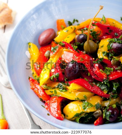 Roasted yellow and red bell pepper salad with capers and olives in a blue bowl on a white background. Grilled vegetables.