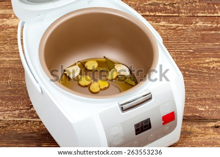 roasting garlic and bay leaf in multicooker closeup - stock photo