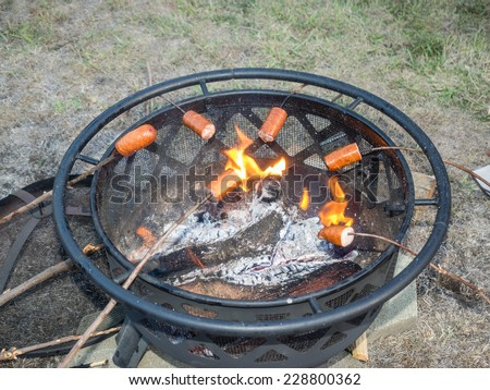 Roasting sausages on wooden sticks over a fire pit - stock photo