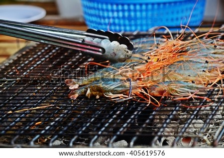 roasting shrimps on gridiron, shrimp barbecue - stock photo