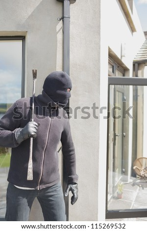 Robber hiding behind a wall with crow bar - stock photo