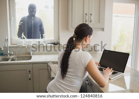 Robber looking at woman in kitchen using laptop through window - stock photo