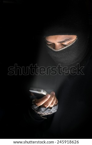 Robber man or hacker watching smart phone. - stock photo