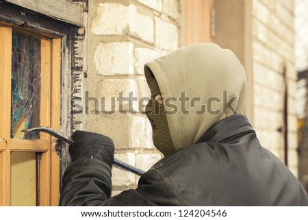 Robber with a crowbar crashed warehouse window - stock photo