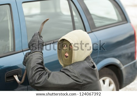 Robber with a crowbar near the car door - stock photo