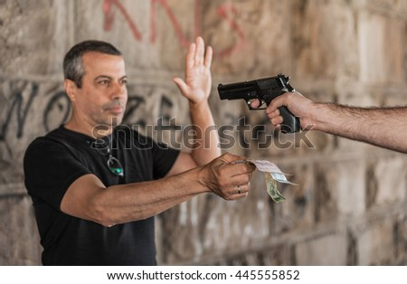 Robber with a gun taking money from victim in a abandoned part of the city - stock photo