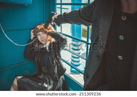 Robber with a gun threatening young beautiful girl. Crime.  - stock photo
