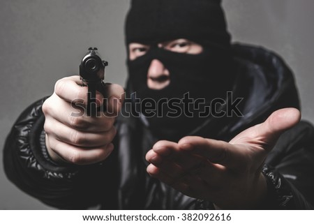 Robber with an aming gun - stock photo