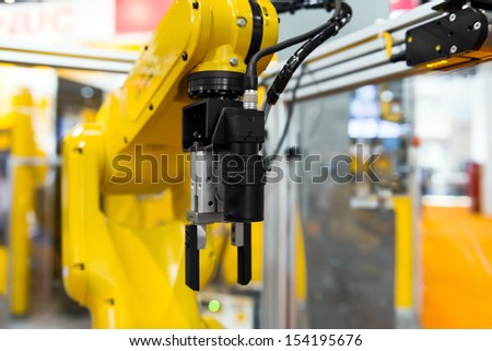 Robot arm in a factory working for the humans - stock photo