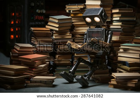 Robot-child reading a book in the workshop of its creator - stock photo