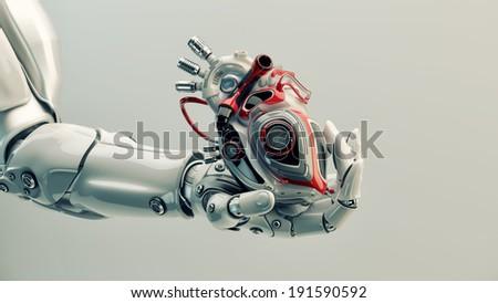 Robot's hand holds robotic heart - stock photo