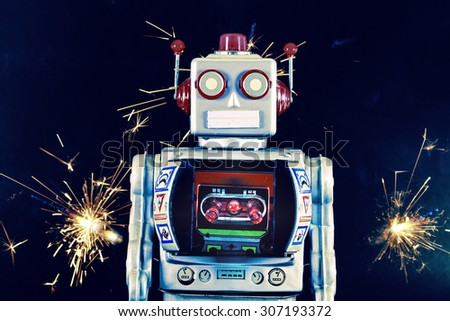 robot toy with sparkes background - stock photo