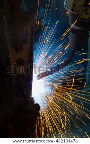 Robot welding automotive part in factory.