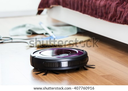 robotic vacuum cleaner cleaning the room - stock photo