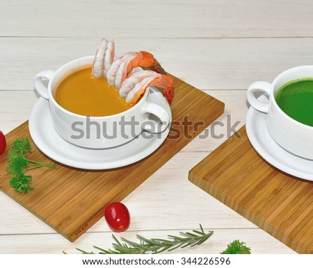 Robster bisques soup with another ingredeints on wood plate - stock photo
