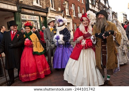 ROCHESTER, UK-DECEMBER 6: Couples dressed in fine Victorian costumes parade in the streets in the annual Rochester Dickensian Christmas Festival,   December 6, 2014, Rochester UK. - stock photo