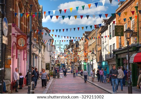 ROCHESTER, UK - MAY 16, 2015: Rochester high street at weekend. People walking through the street, passing cafes, restaurants and shops - stock photo