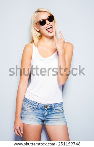Rock and Roll queen. Beautiful young blond hair women making a face and gesturing while standing against grey background   - stock photo