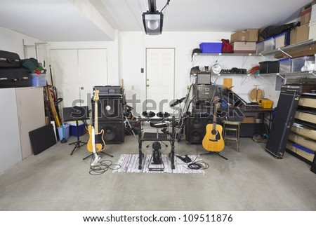 Rock band music equipment in a cluttered suburban garage.