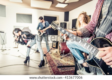 Rock band recording a music track in a studio - Friends performing music in a recording studio - stock photo