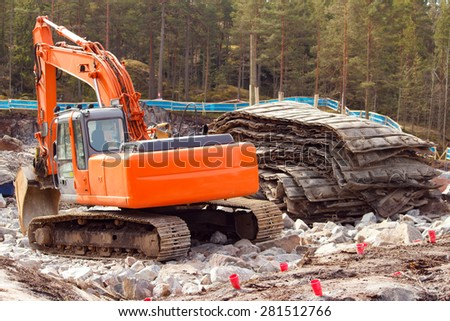 Rock blasting site area closeup , blast protection rubber mats on right , drilled holes for dynamite with red cones on foreground - stock photo