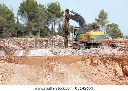 Rock Breaker: Rock breaker in action on difficult soil - all brand names removed. - stock photo