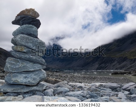 Rock cairn in Hooker Valley on a trail leading to Aoraki  Mount Cook  highest peak of Southern Alps  an icon of New Zealand covered in clouds - stock photo