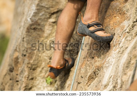 Rock climber about to start climbing his route, bottom view with his foot on the foreground - stock photo