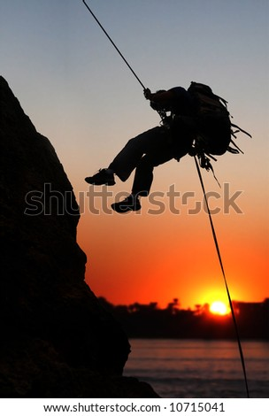 rock climber at sunset time going up a mountain - stock photo
