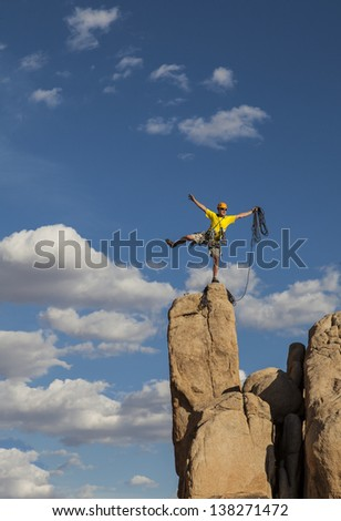 Rock climber balances on the summit after a successful and challenging ascent.