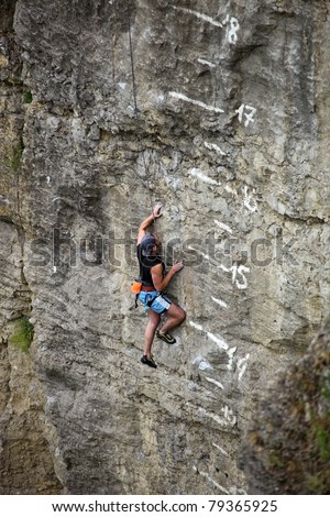 Rock climber battling his way up cliff - stock photo