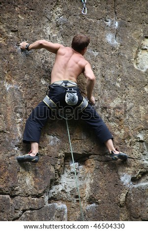 Rock climber climbing at the rock - stock photo