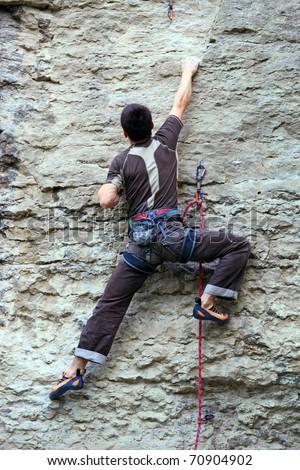 Rock climber climbing up a cliff - stock photo