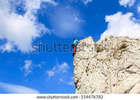 Rock climber climbing white limestone rock in Jura Plateau with blue sky and clouds in background, Poland - stock photo